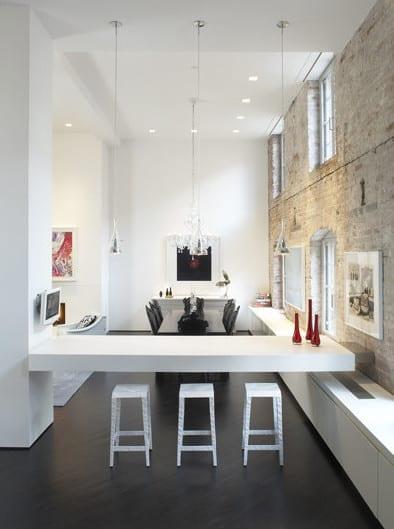 moderne loft wohnung mit unverputzter natursteinwand und weißen putzwänden_modernes wohnesszimmer mit küche weiß und bartheke weiß