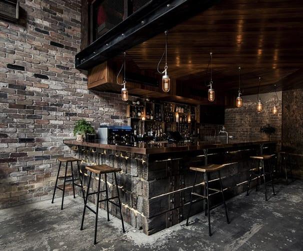 estrichboden und graue ziegelwand für moderne raumgestaltung und wohnzimmer design mit eckbar aus Holzbalken und industrial style-barhockern
