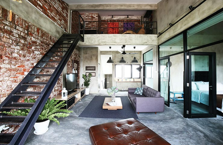 Mezzanin-Loft im industrial style mit unverputzten wänden und wohnzimmer mit glaswand zum schlafzimmer mit estrich als bodenbelag