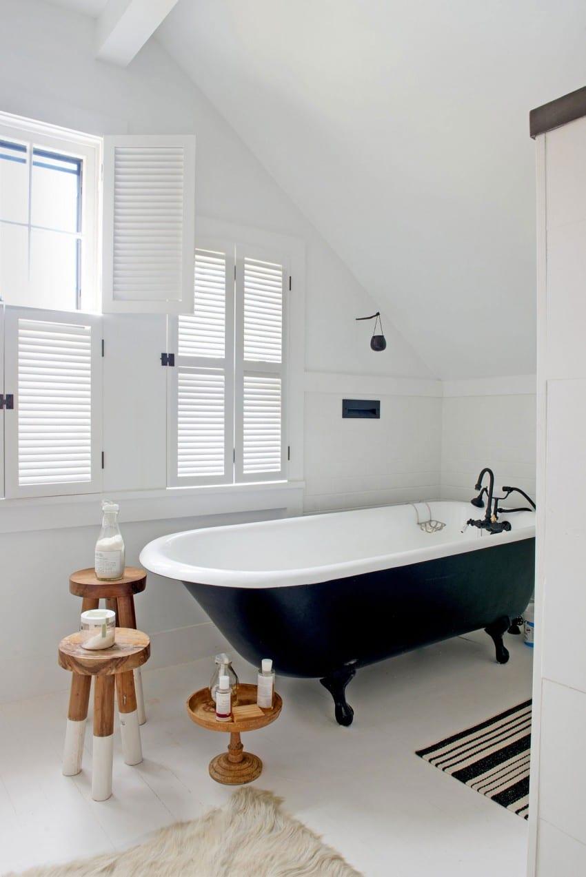 moderne badezimmer mit dachschräge und freistehender vintage-badewanne schwarz mit schwarzen Klauenfüßen und drei holzhocker aks beistelltische
