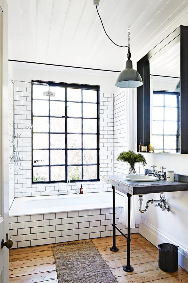 kleines badezimmer mit badewanne und weißen fliesen mit schwarzer fuge