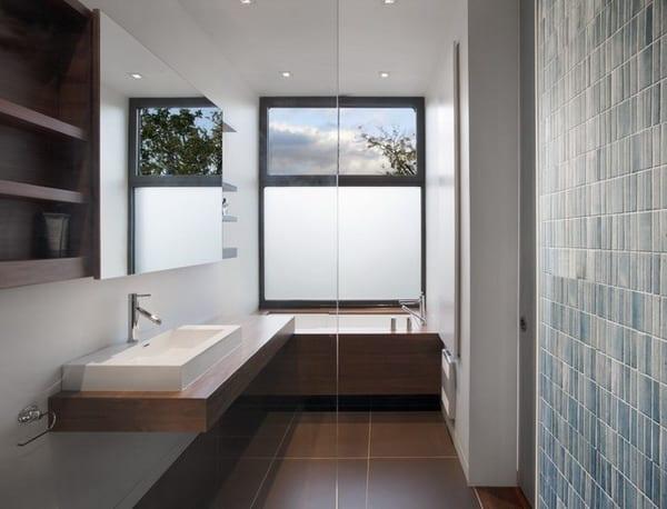 kleine und enge badezimmer mit waschtisch aus holz und japanische badewanne mit holzverkleidung vor dem fenster