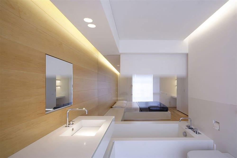 modernes badezimmer mit glaswand zum schlafzimmer und japanische badewanne