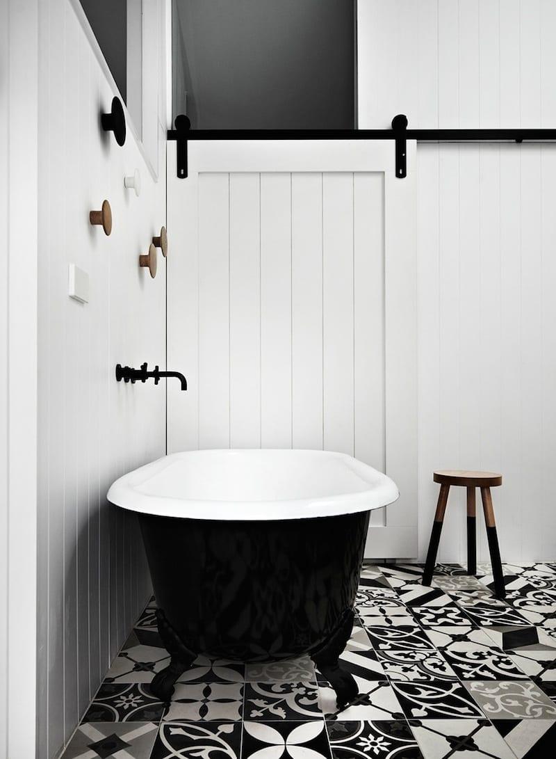modernes badezimmer mit schiebeholztür weiß und vintage-Badewanne schwarz