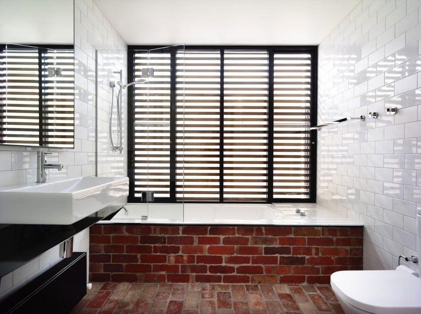 modernes bad mit badewanne und fenster mit schwarzen fensterrahmen und sonnenschutzlamellen
