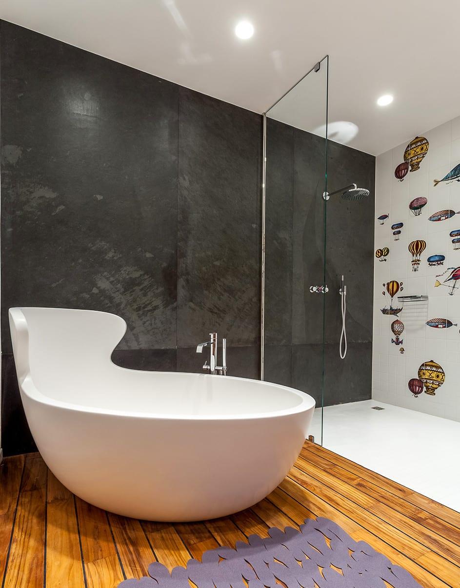 modernes badezimmer mit schwarzer akzentwand und dusche mit glaswand und weißen fliesen mit luftballons