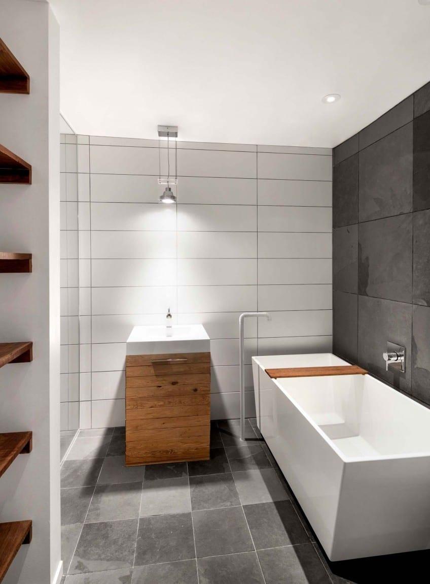 moderne badezimmer mit schwarzen und weißen wandfliesen und designer-badewanne freistehend und holzwaschtischschrank beleuchtet mit pendellampe