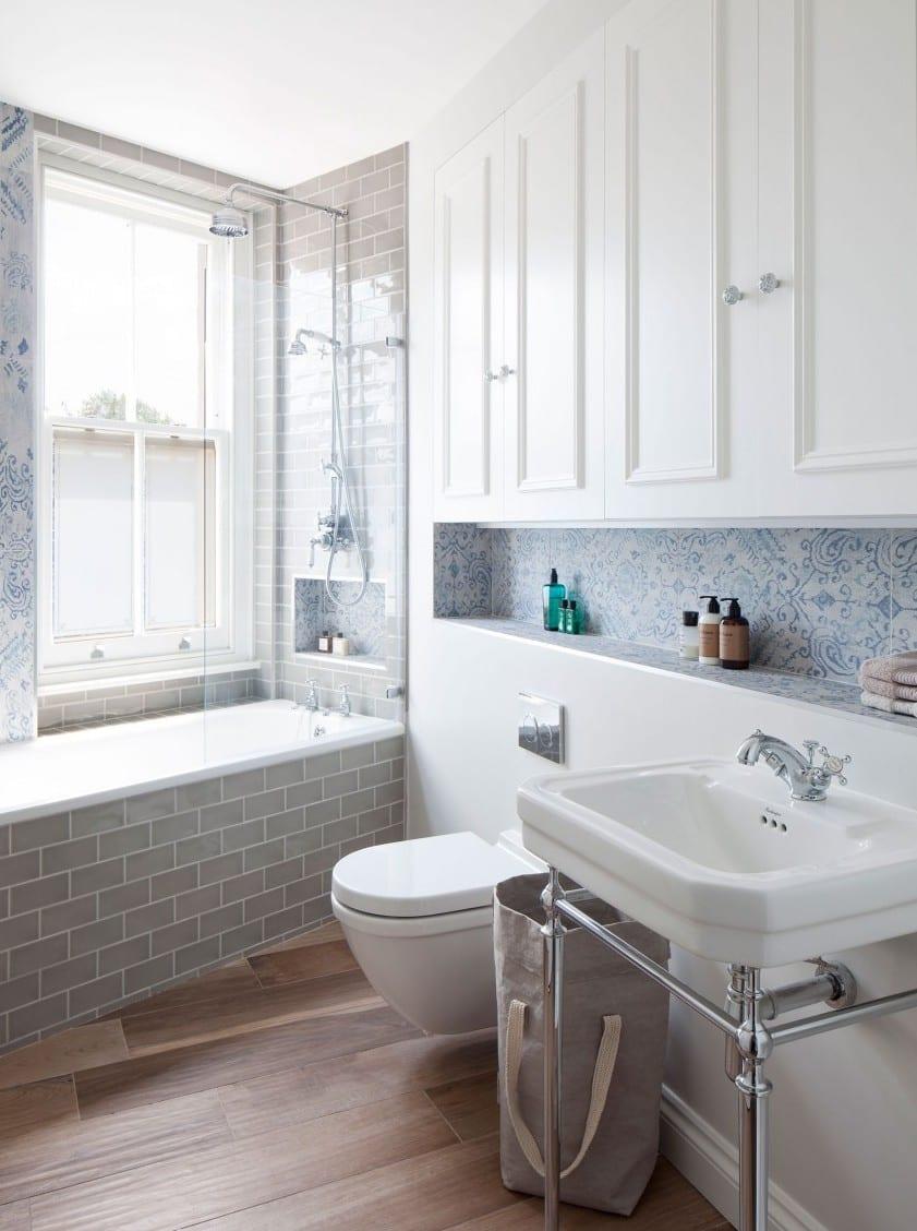 kleines badezimmer kreativ einrichten mit badewanne und weißen eingebaiten wandschränken und modern gestalten mit weißen wandfliesen mit blaumem blumenmuster