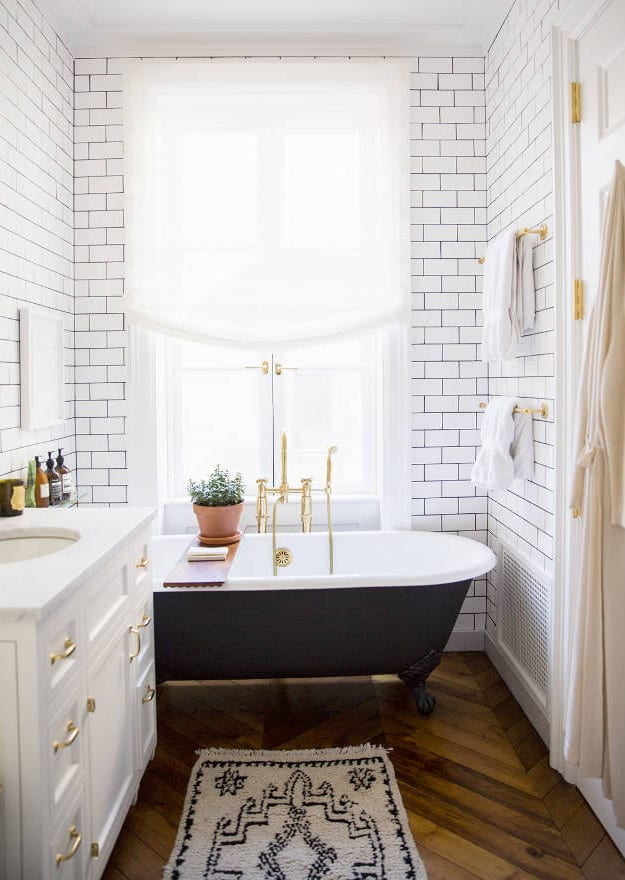 kleines bad modern gestelaten mit parkett und weißen badezimmerfliesen_fenster im bad und freistehende vintage-badewanne schwarz vor dem fenster mit goldenen badtuchhaltern