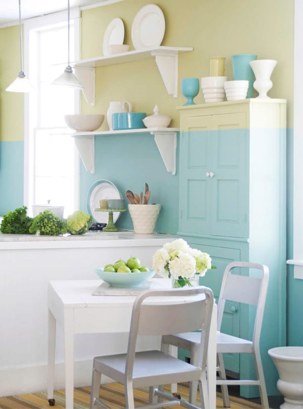 küche streichen in hellblau und hellgelb_kreative wandgestaltung und farbgestaltung mit wandfarbe blau und wandfarbe gelb_kleine küche einrichten mit kochinsel weiß und kleinem holzesstisch mit weißen stühlen und weiße holzwandregalen