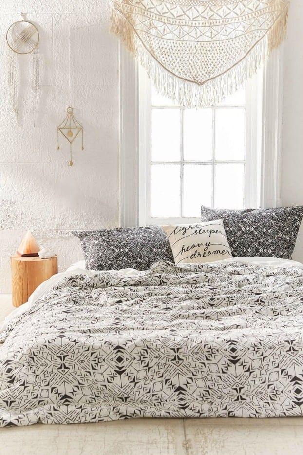 weißes schlafzimmer interior mit edler bettwäsche weiss und nachttisch aus rundholz
