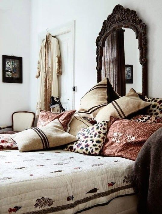 boho chic style im schlafzimmer gestalten mit vielen kissen als bettdeko und wanddeko mit spiegel mit Holzrahmen
