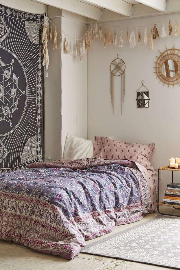 schöner wohnen schlafzimmer in boho chic style mit schöner bettwäsche in hellrosa und lila und kreative wansgestaltung schlafzimmer mit gemusterten textilwaren und diy- troddel-gerlande
