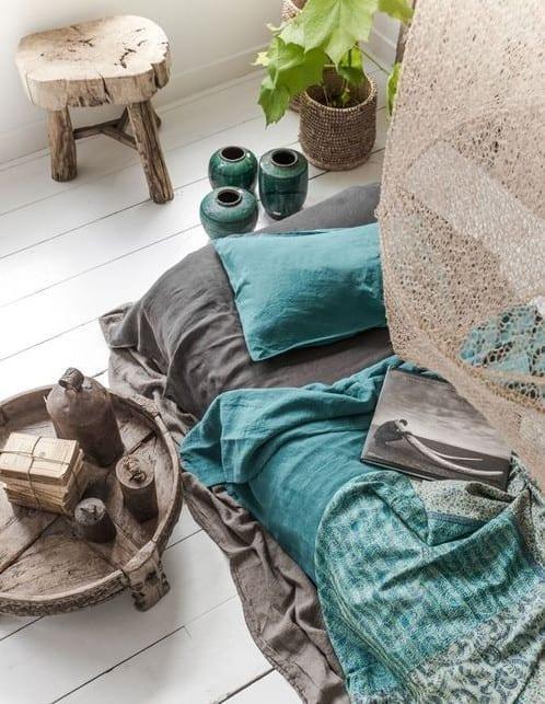 schöne bettwäsche grau und blau kombiniert mit blauen blumenvasen und rustikalen Holzhocker und Beistelltisch rund