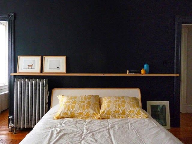 schlafzimmer gestalten mit schwarzer wandfarbe und holzwandregal hinter dem bett