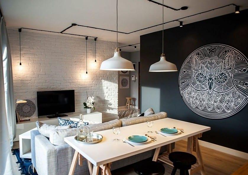 kleine wohnungen modern und kreativ gestalten mit ziegelwand weiß und akzentwand schwarz_moderne pendelleuchten schwarz und weiße pendellampen über dem holzesstisch im kleinem wohnesszimmer mit soffa grau und couchtisch weiß