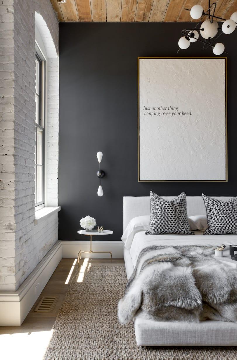 kleine schlafzimmer modern einrichten mit weißem bett und designer wand- und pendelleuchten_moderne raumgestaltung mit holzfußboden und holzdecke as akzent zur weißen ziegelwand und schwarzer wandfarbe