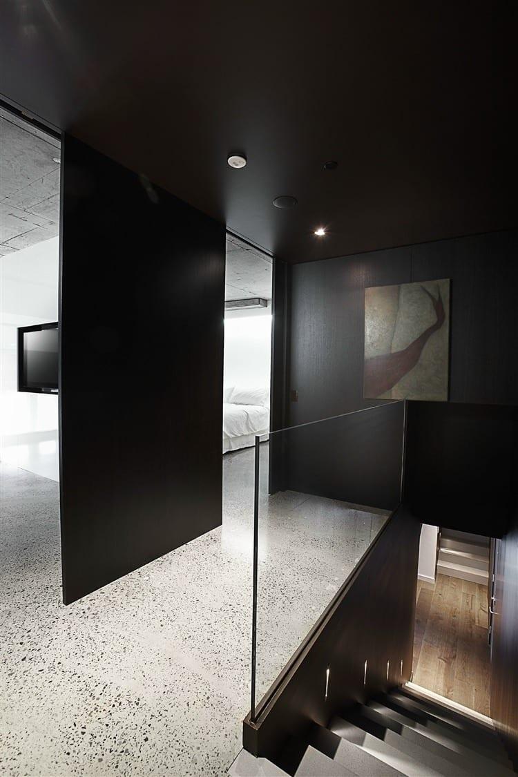minimalistisches interior design mit schwarzen wänden und innentreppe holz mit glastreppengeländer