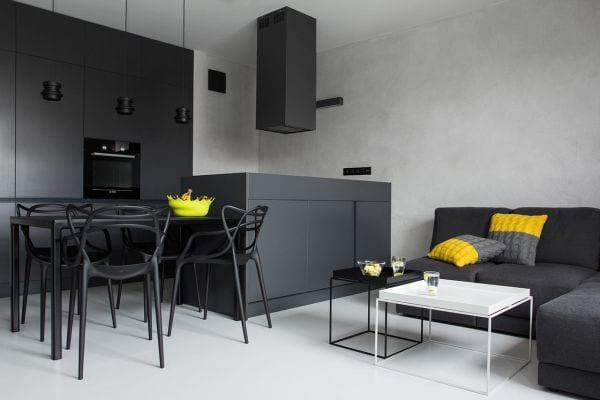 kleine wohnung modern einrichten mit schwarzem ecksofa und esstisch mit esstischstühlen schwarz_kleine küche mit kochinsel und küchenschränken schwarz