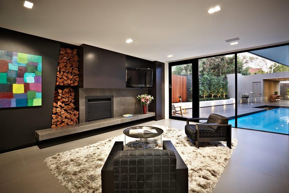 wohnzimmer design in schwarz_geposterte schwarze sessel mit rundem couchtisch für moderne einrichtung wohnzimmer mit kamin und wandregal aus beton