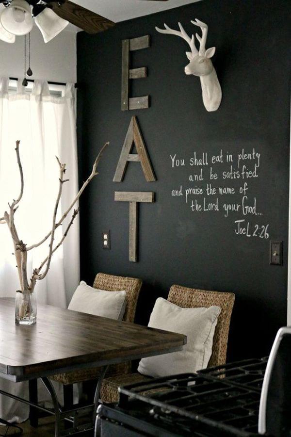 coole einrichtung für kleine küchen mit schwarzer wand und holzbuchstaben als kreative wandgestaltung küche_rustikale küchengestaltung mit holzesstisch und ratanstühlen