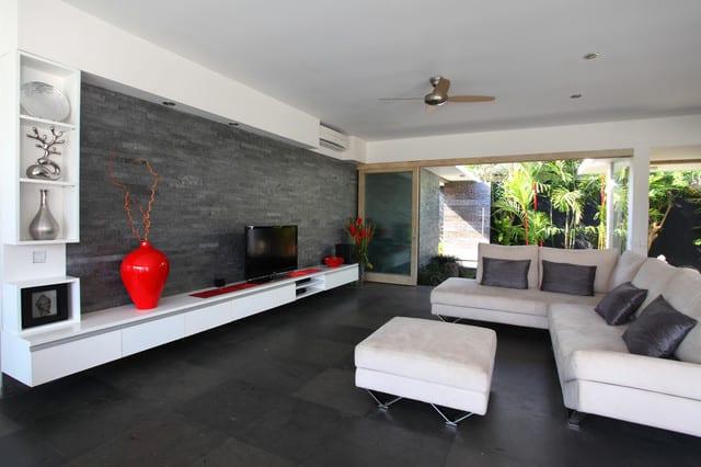 schwarze natursteinwand als akzentwand im wohnzimmer mit moderner wohnwand weiß und und roten dekoelementen