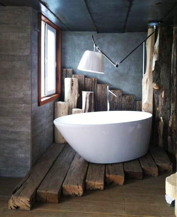badezimmer modern im vintage stil einrichten mit designer deckenlampe über freistehende badewanne_badezimmer mit betonwänden und holzbalken-podest