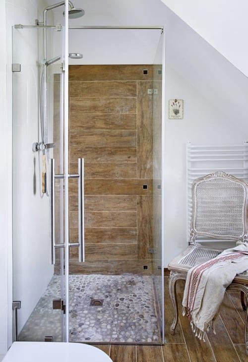 kleines badezimmer mit dachschräge und duschkabine mit kiselsteinboden und vintage holzstuhl