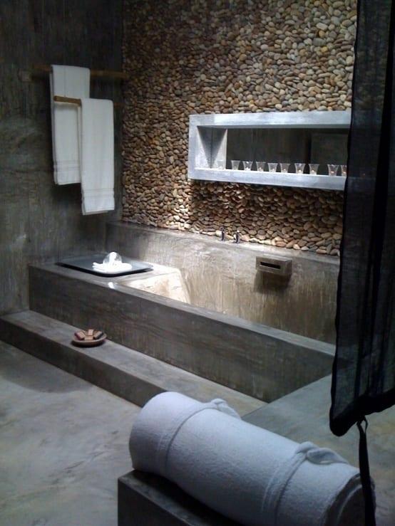 badezimmer modern mit wandgestaltung aus Kieselsteinen und beton- badewanne ausgemauert