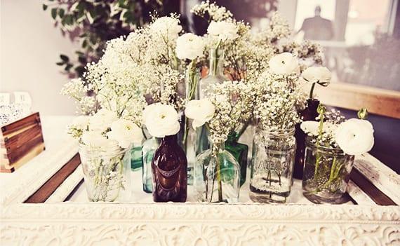 tischdeko blumen im vintage style_originelle tischdekoration mit weißen blumen in glasgefäßen und vintage Rahmen