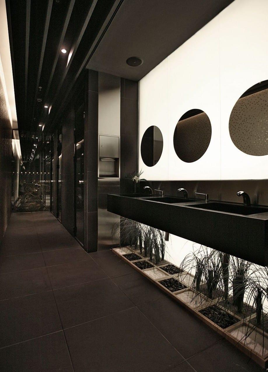 moderne badezimmer schwarz mit runden badezimmerspiegeln und dekorativem steingarten unter dem betonwaschtisch