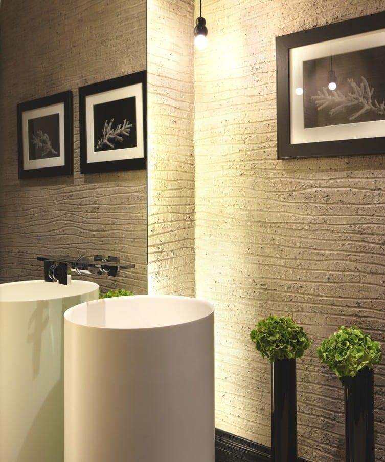 modernes badezimmer interior mit texturierten betobwänden und Pendellampe_schwarze blumenvasen und bilderrahmen als baddeko