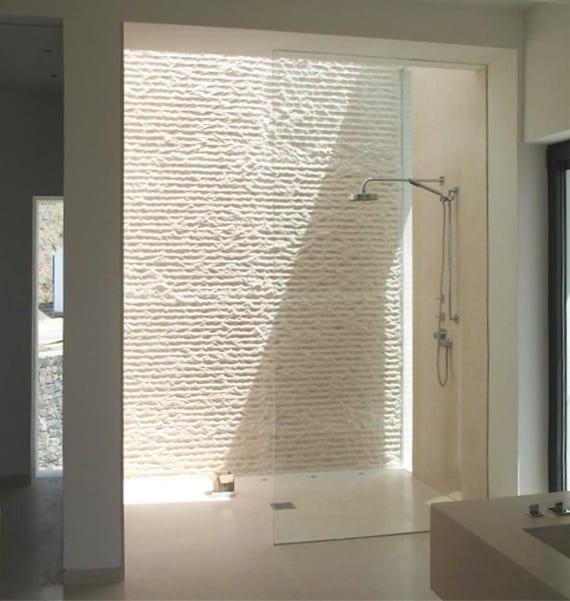 modernes badezimmer mit dachverglasung im duschbereich und wandverkleidung mit naturstein weiß