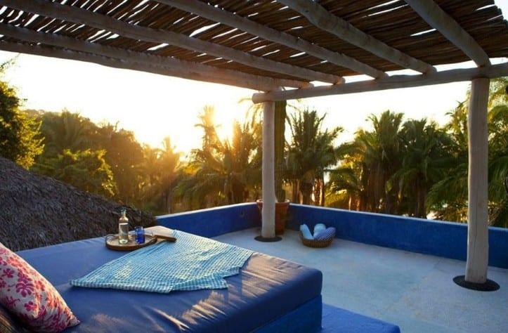 oase auf dachterrasse mit polster-tagesbett unter tarrassenüberdachzng aus rundholzern
