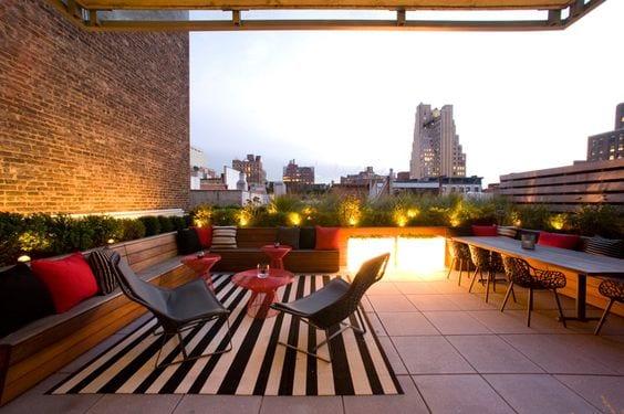 moderne roof top terrasse mit begrünung und holzsitzbänken_dachterrasse gestalten mit terrassenmäbeln in schwarz und rot