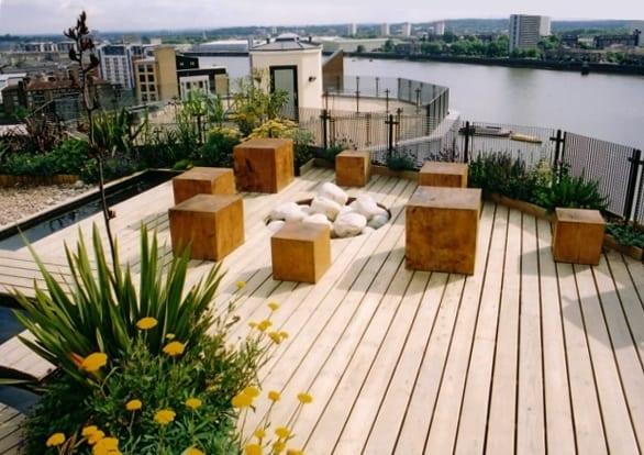 dachgarten ideen mit holzdiele und teichbecken_roof top ideen für terrassen mit feuerstelle aus steinen und holzhockern