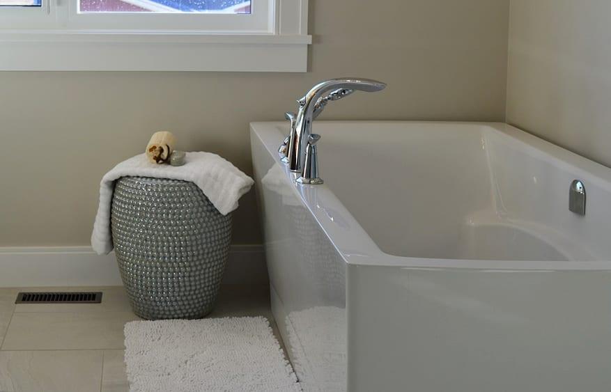 badausstattung kleiner badezimmer mit weißer badewanne und badematte und silbernem hocker als beistelltisch_kleine badezimmer gestalten mit wandfarbe beige und Fliese in Beige