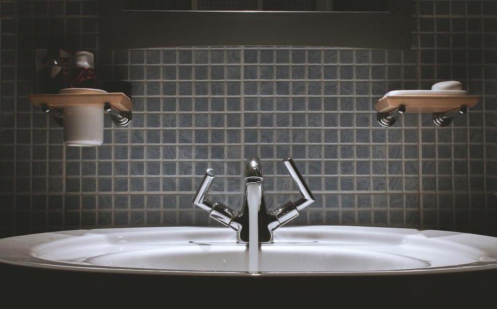 bad modern gestalten mit schwarzen mosaikfliesen, rundem waschbecken und modernen zahnbuerstenhalter und seifenbehälter für wand