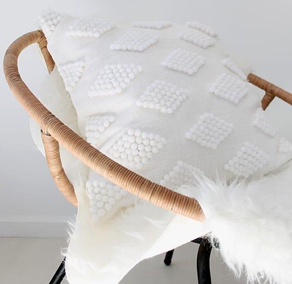 skandinavische dekoidee mit diy kissen weiß und feltdecke weiß