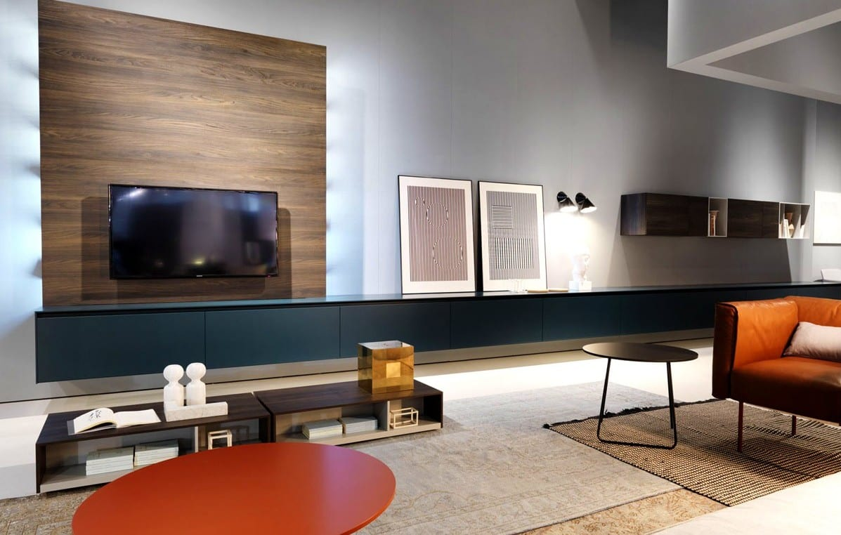 elegantes wohnzimmer design mit wandgehängtem lowboard und tvwand aus holz mit indirekter beleuchtung als wohnidee für modernes wohnzimmer mit ledersofa und rund couchtisch in orange