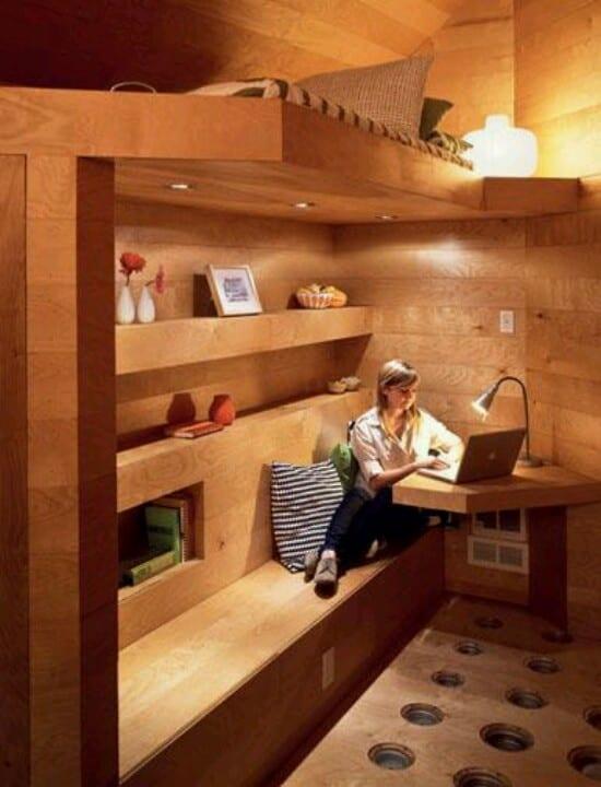 kleines schlafzimmer in holz mit hochbett und kleiner sitz- und arbeitzecke