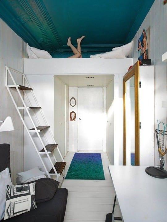 studentenzimmer und kleines schlafzimmer einrichten mit hochbet und gestalten mit blauer decke als akzent zu den weißen möbeln und sofa grau