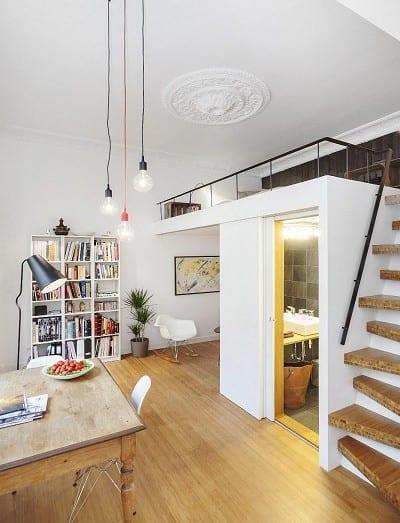einzimmerwohnung einrichten ideen mit loft bed über badezimmer und pendelleuchten über esstisch holz