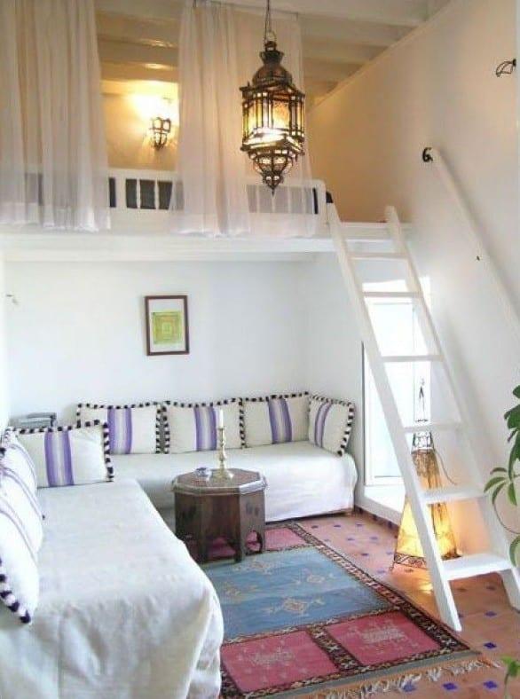 hochbett weiß mit holzleiter und gardienen über kleinem wohnzimmer in marokkanischem stil mit rundem couchtisch