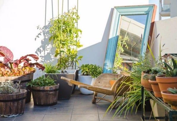 dachterrasse gestalten als urban garden mit rustikalem spiegel und großen runden holzeimern als blumenkübel