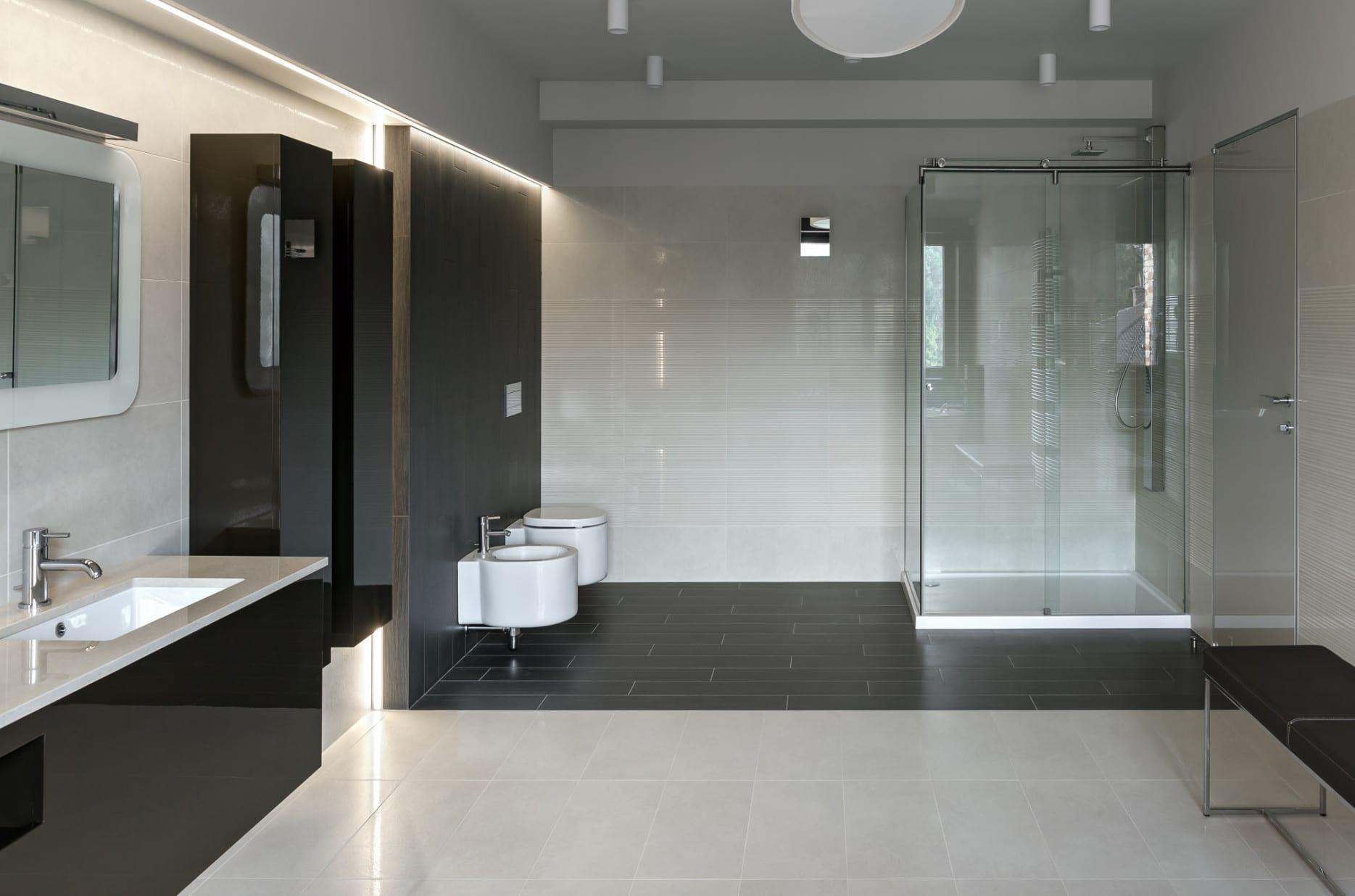 modernes bad mit schwarzen und weißen badfliesen, waschtisch und wandschränke in hochglanz schwarz und einbaudeckenleuchte