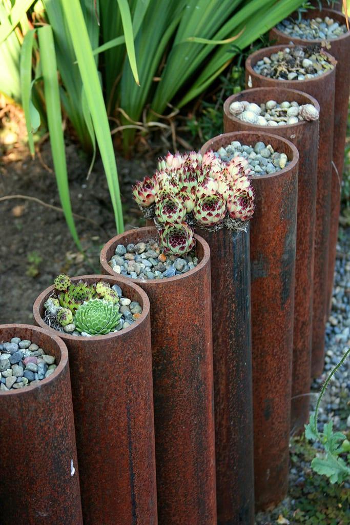 originelle gartengestaltung mit stahlröhren als pflanzenkübel und rasenkante