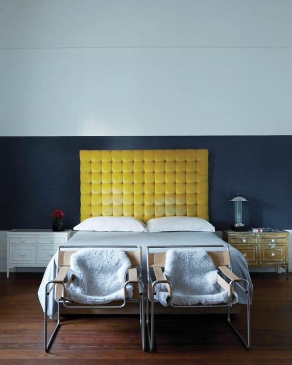 schlafzimmer wandfarbe weiß und dunkelblau kombiniert mit vintage nachttischen holz und gepolstertem bettkopfteil gelb