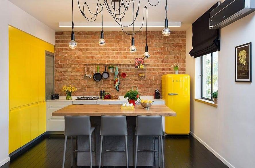 moderne kücheneinrichtung mit weißen küchenschräbken und holzesstisch mit grauen barstühlen und akzentwände in gelb und ziegeln