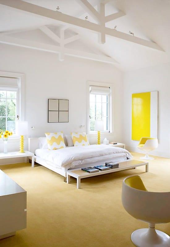moderne schlafzimmer in weiß mit gelben dekoelementen wie kissen, tischlampen und bilder